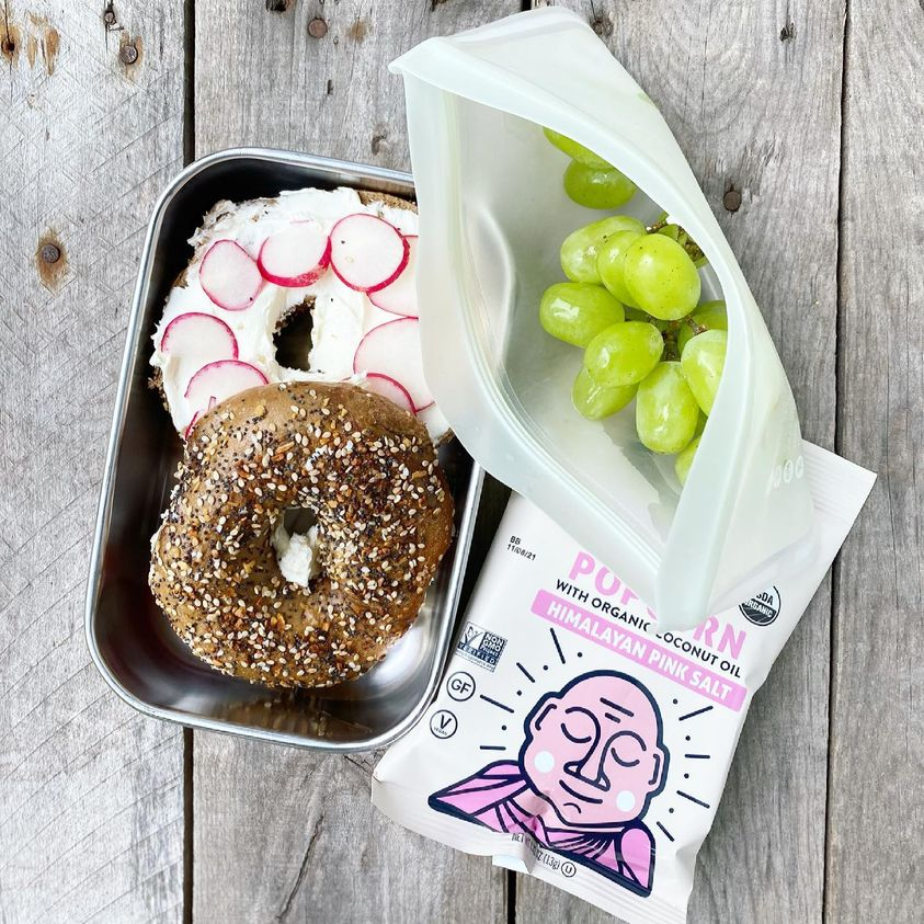 Packed school lunch that includes a whole-wheat bagel topped with cream cheese and radishes, grapes, and popcorn.