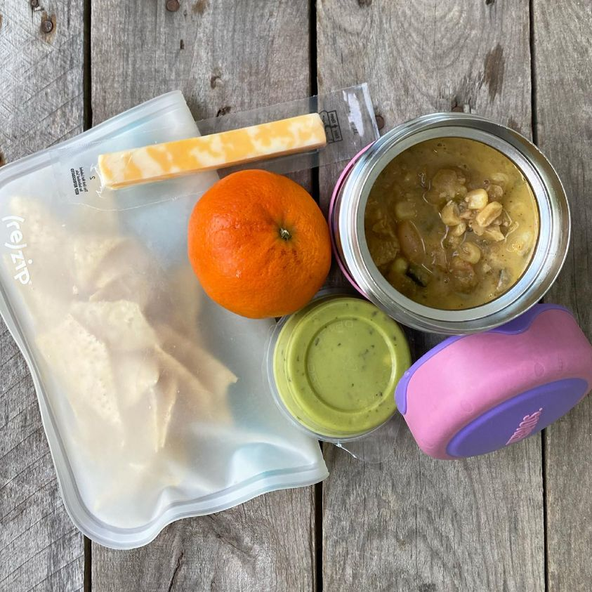 Packed school lunch that includes White Chicken Chili in a thermos, tortilla chips, guacamole, orange, and a cheese stick.