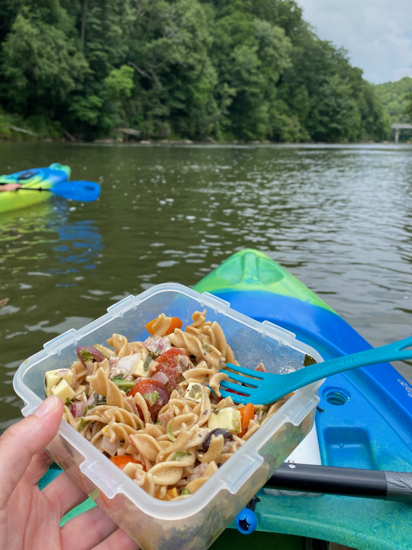 Holding a container of pasta salad while sitting in a kayak on the water from a persons viewpoint.