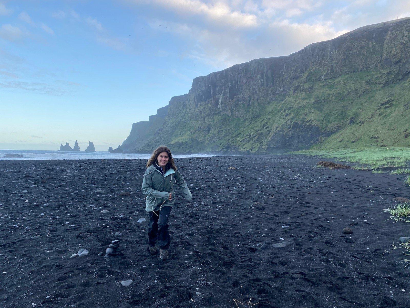 Teen girl running on black beach in Iceland.
