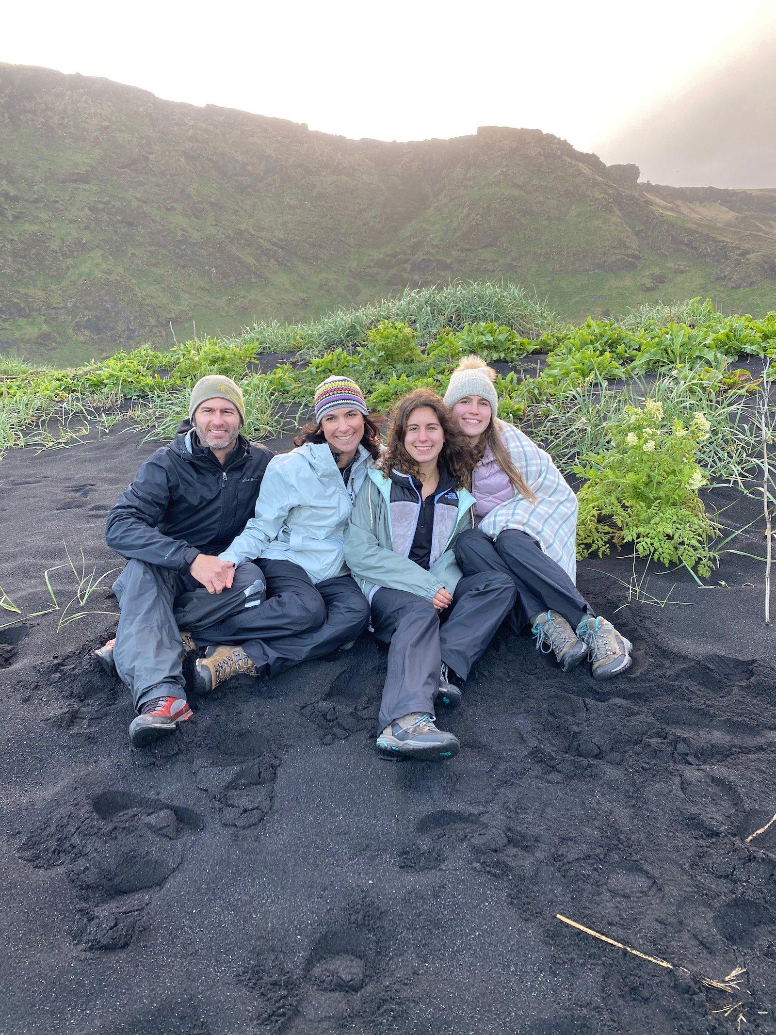 Family posing on black beach in Iceland.
