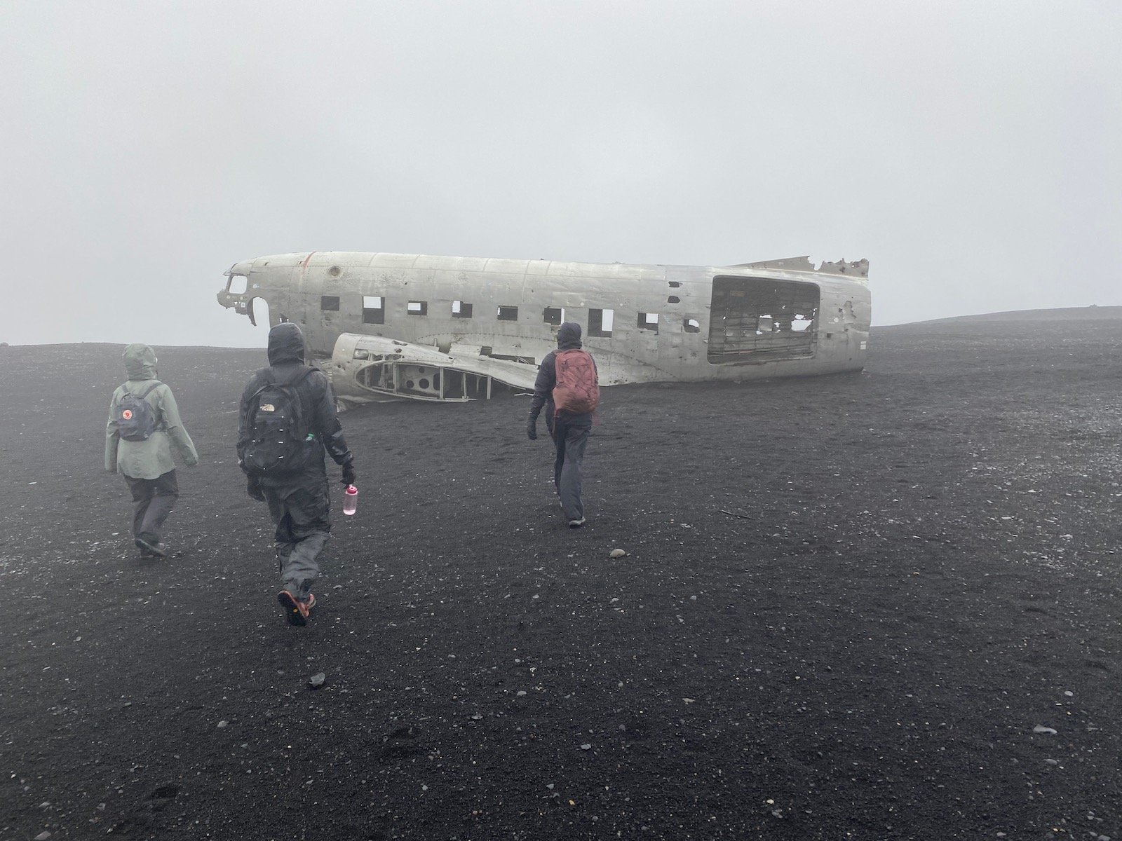Family walking towards the famed 1973 plane wreck in Iceland.