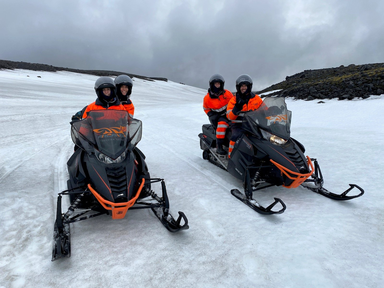 Family posing on snowmobiles in Iceland.
