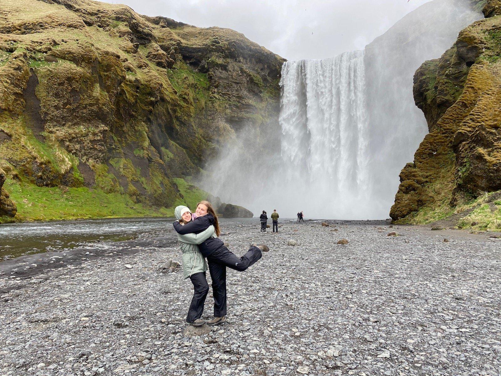 Sisters posing at Skógafoss Falls near Vik in Iceland.