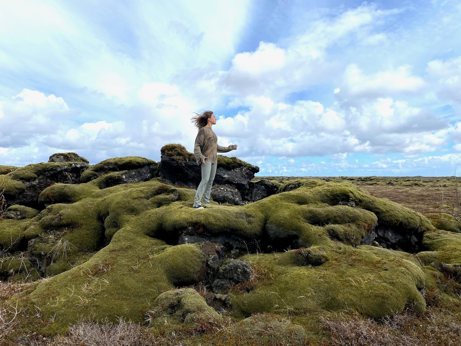 Teen girl standing on moss covered mounds in Iceland.