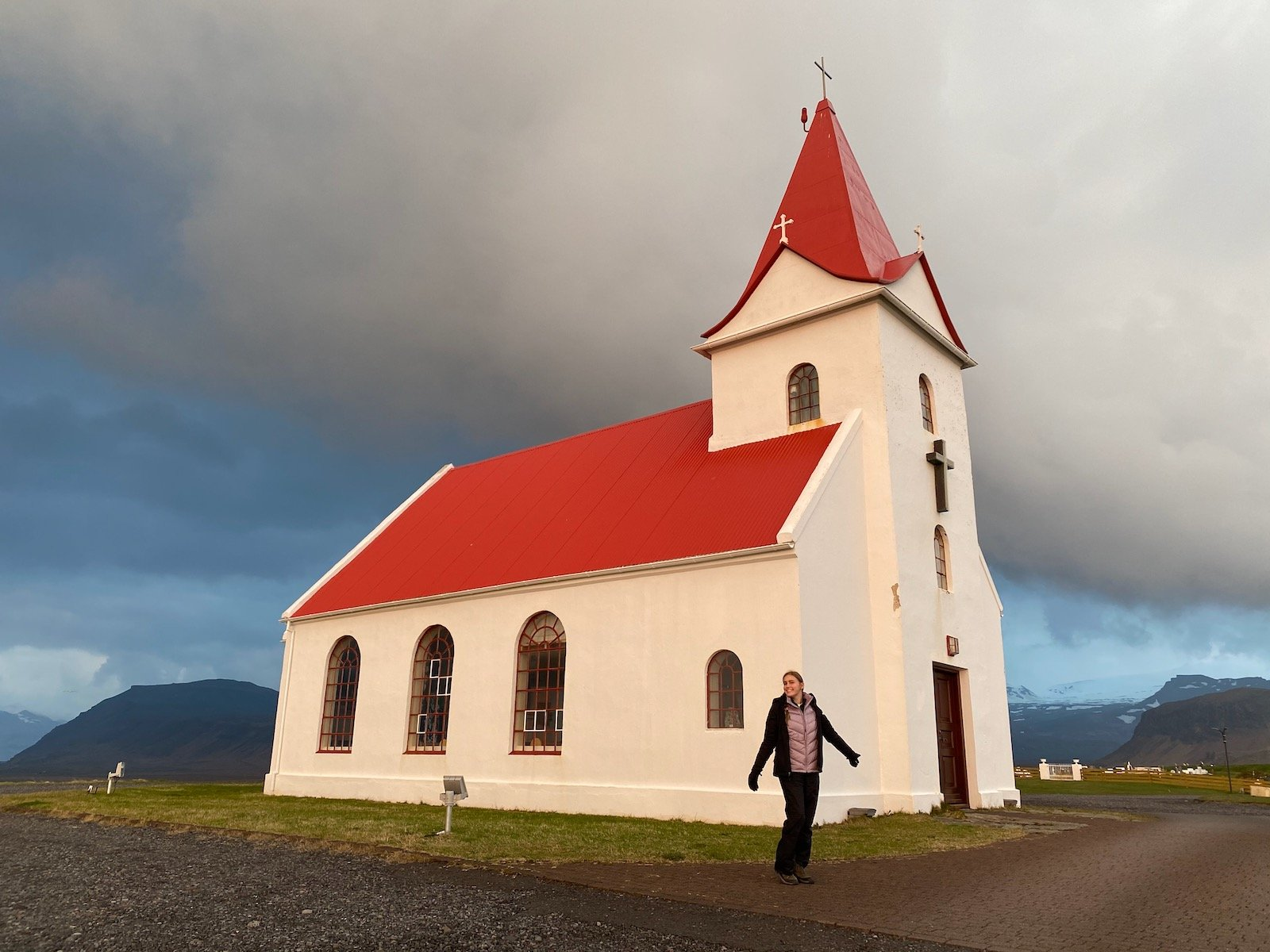Teen girl posing in front of a quaint little church in Iceland.