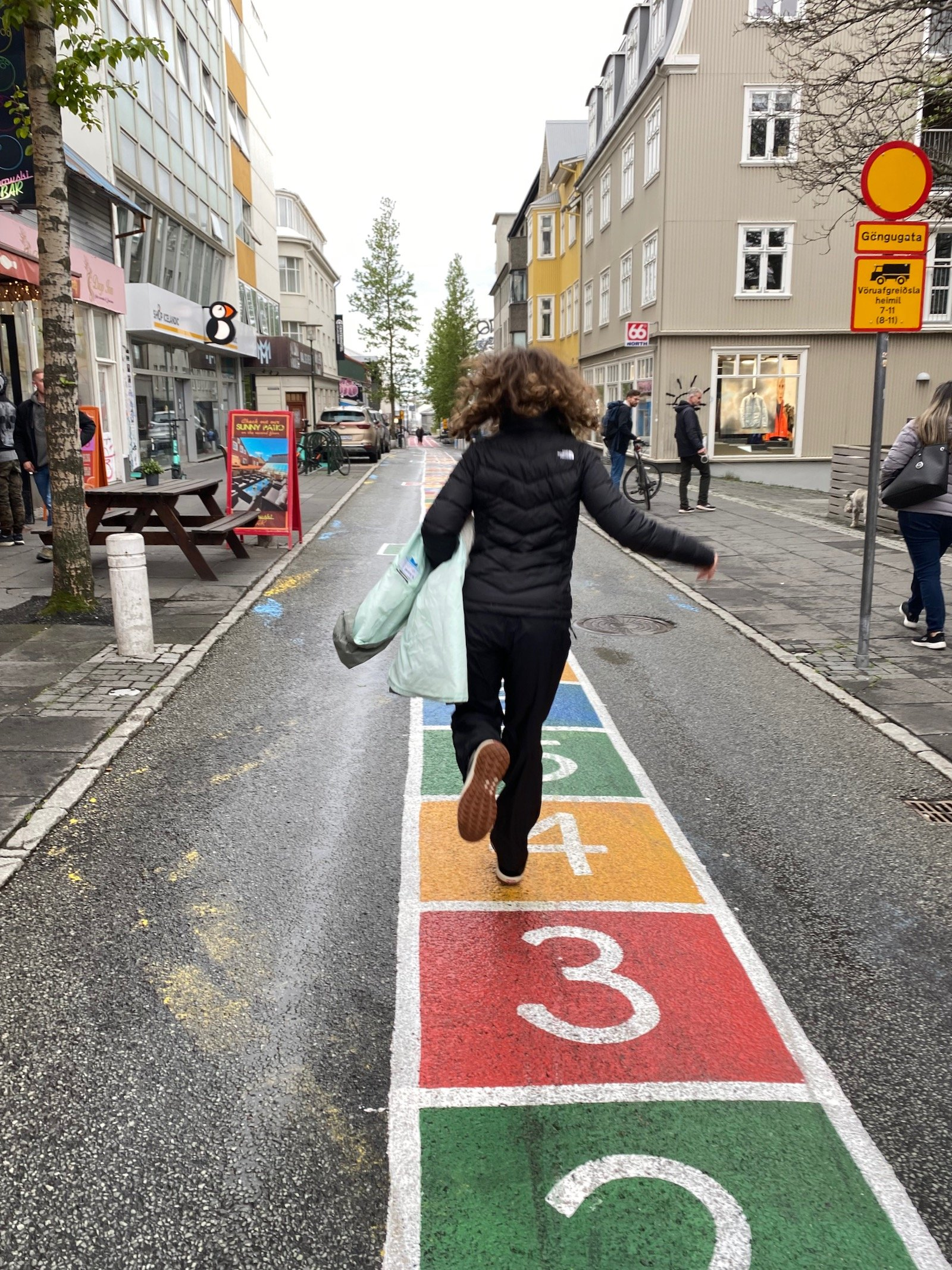 Teen girl hopping in the streets of Reykjavík.