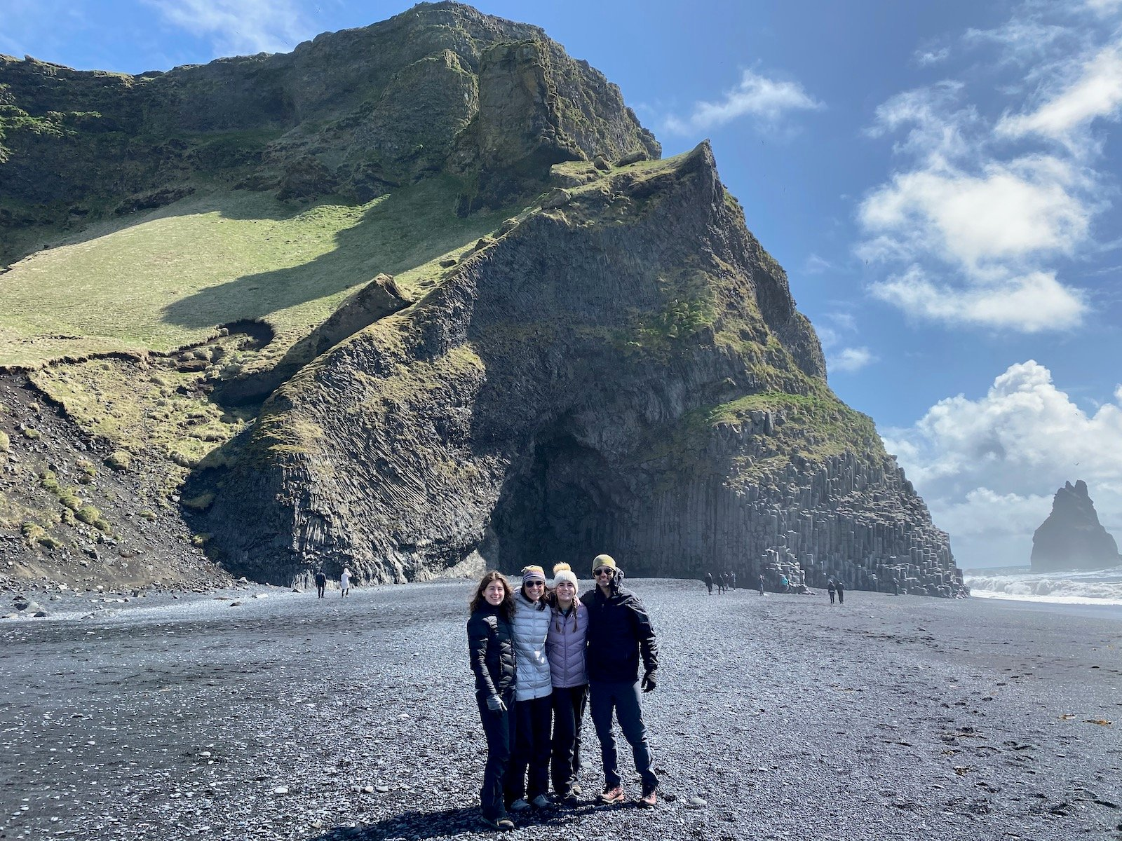 Family posing on beach in front of Basalt Columns in Iceland.