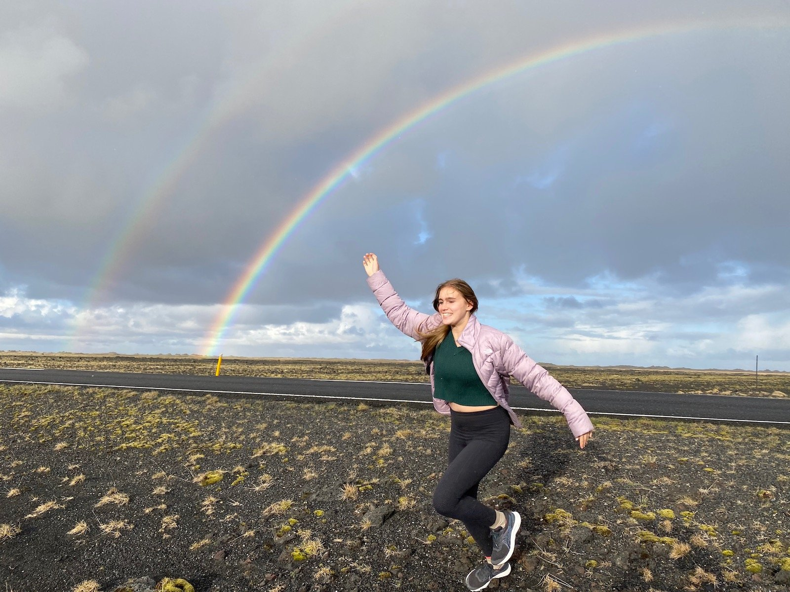 Teen girl in field with double rainbow in the background in Iceland.