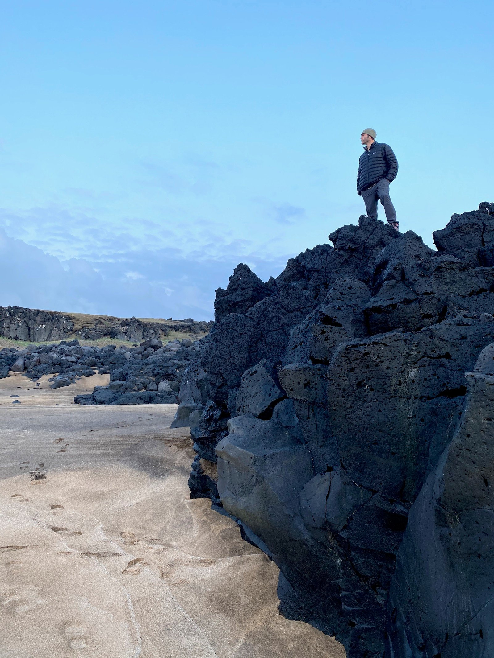 Father posing on top of black rocks at the White Sand beaches in Snæfellsjökull National Park.