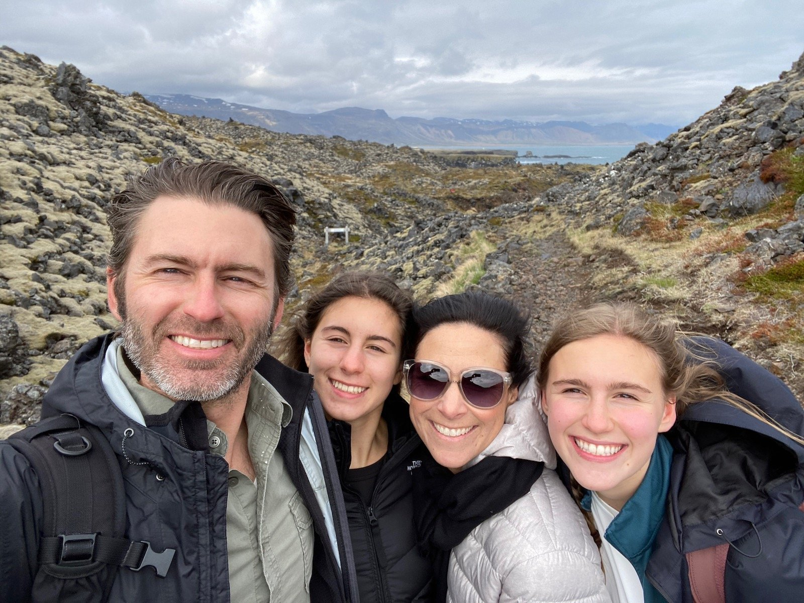 Family portrait with scenic views in the background in Iceland.