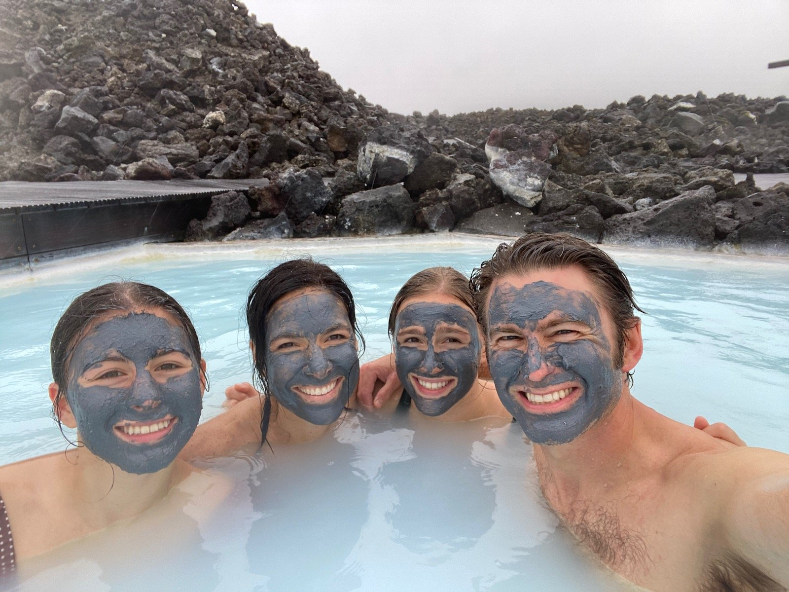 Family posing with mud masks on in the Blue Lagoon in Iceland.