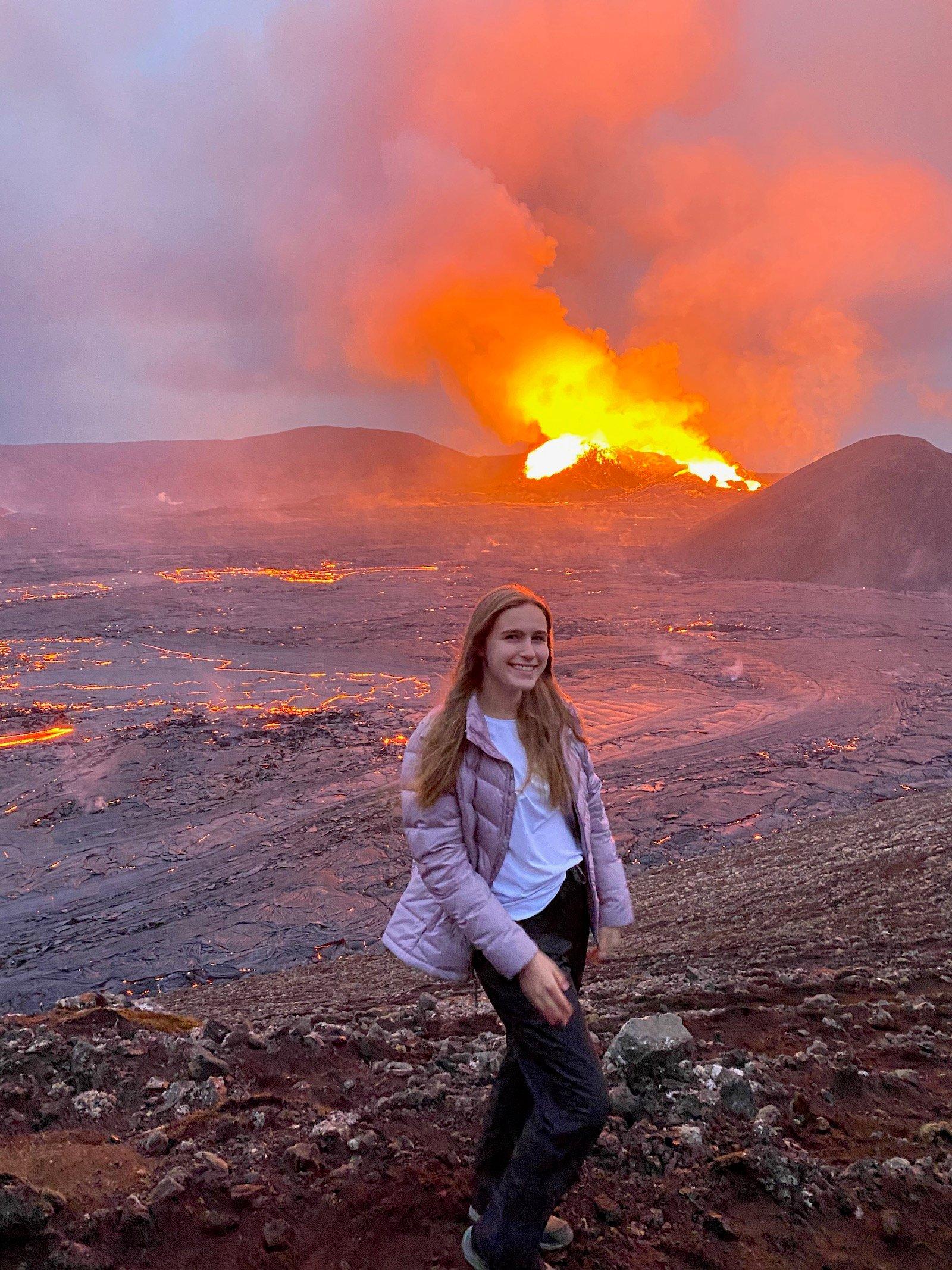 Teen girl posing in front of the erupting Fagradalsfjall Volcano.