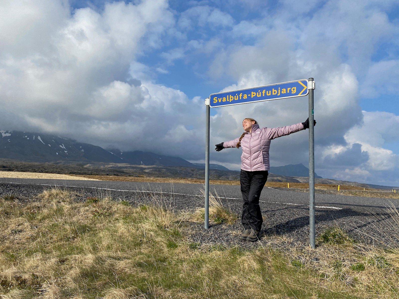 Teen girl posing under sign of Snæfellsjökull National Park.