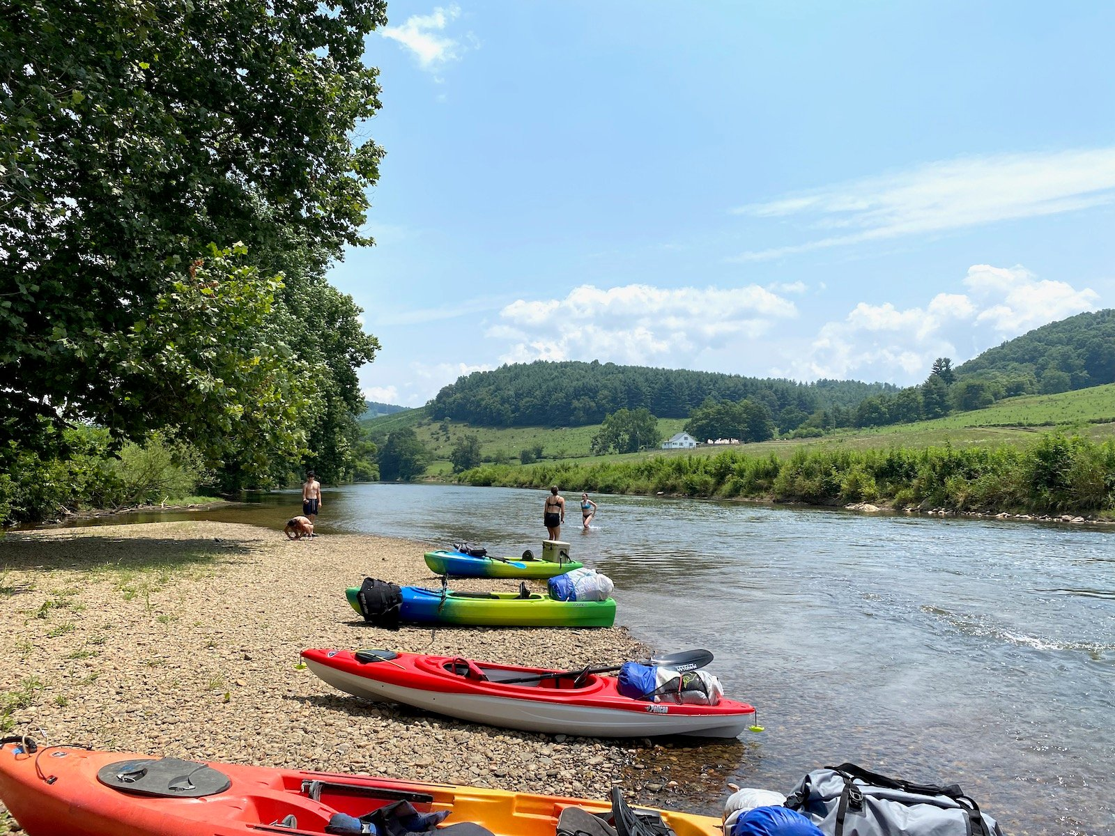 Four kayaks lined up on the banks of the river in North Carolina.