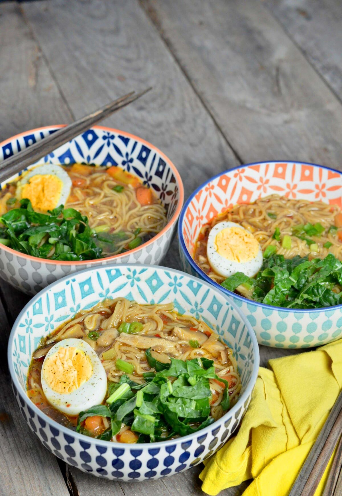 Three decorative bowls with homemade ramen on a table.